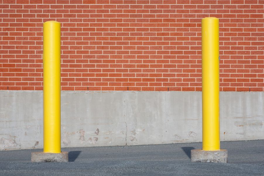 Yellow traffic bollards in front of brick building wall.